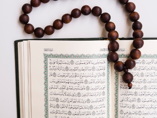 Top shot close up opened quran with prayer beads