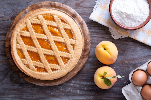 Верхний снимок абрикосового пирога со свежими яйцами и миской муки на деревянной поверхности