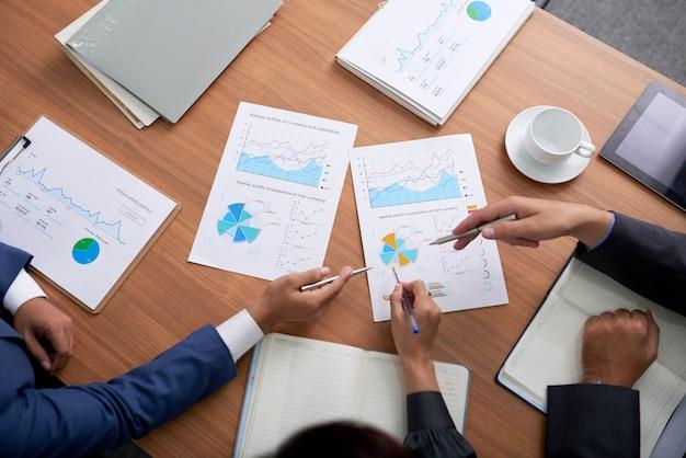 Топ снимок трех неузнаваемых деловых людей, сидящих на встрече и смотрящих на диаграммы