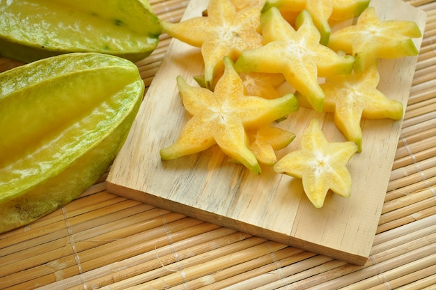 Top shot of starfruit and its slices on a wooden chopping board