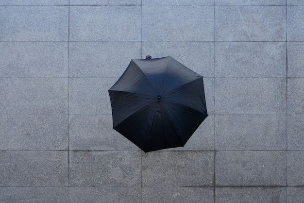 Top shot of unrecognizable person standing under umbrella on pavement