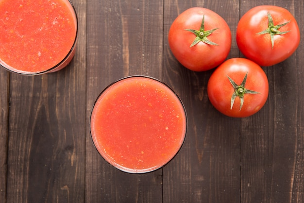 Top shot vegetable smoothie made of red ripe tomatoes on wooden table