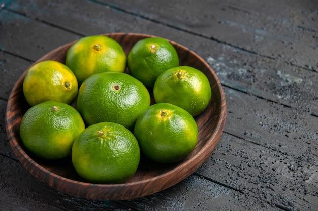 Крупным планом вид сверху зелено-желтых лаймов в тарелке зелено-желтых лаймов в тарелке на сером столе
