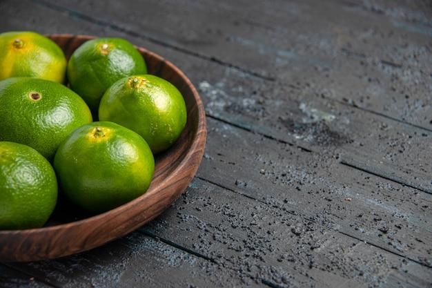 Vista ravvicinata del lato superiore lime sul tavolo lime verde-giallo in una ciotola sul tavolo grigio