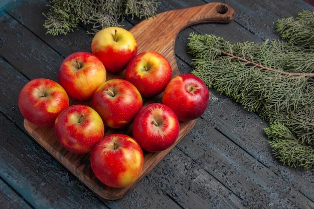 木の枝の間の灰色の表面のまな板の上に9つの黄赤リンゴが乗っている上面の拡大図の果物