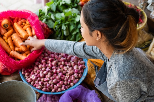Top side view of an asian greengrocer holding a carrot in a sack at a vegetable stall