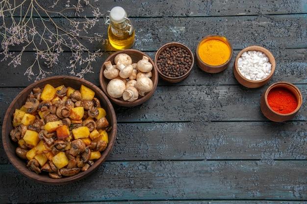 白いキノコの横にあるキノコとジャガイモの木製ボウルは、カラフルなスパイスと枝に油をさします