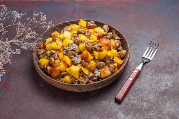 ジャガイモとキノコのボウルと暗い表面にフォークが付いているジャガイモの上面図ボウル