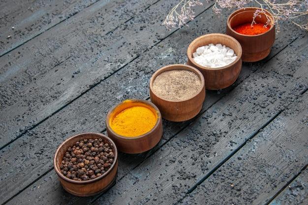 Vista laterale dall'alto spezie colorate diverse spezie colorate al centro del tavolo