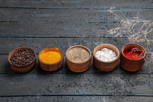 Vista laterale dall'alto spezie colorate una fila di diverse spezie colorate al centro del tavolo