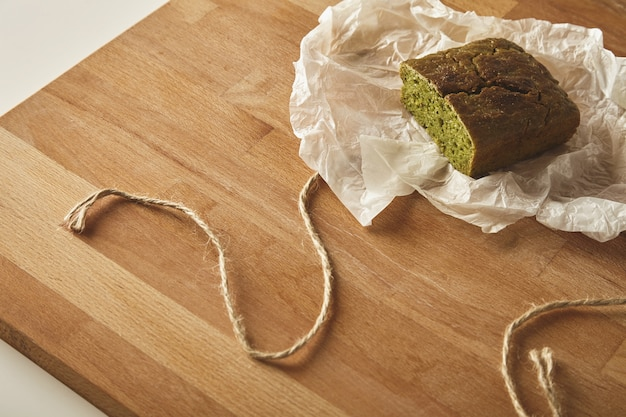 クラフト紙のテーブルの上の木の板に分離された健康的な食事ほうれん草のパンの上面図