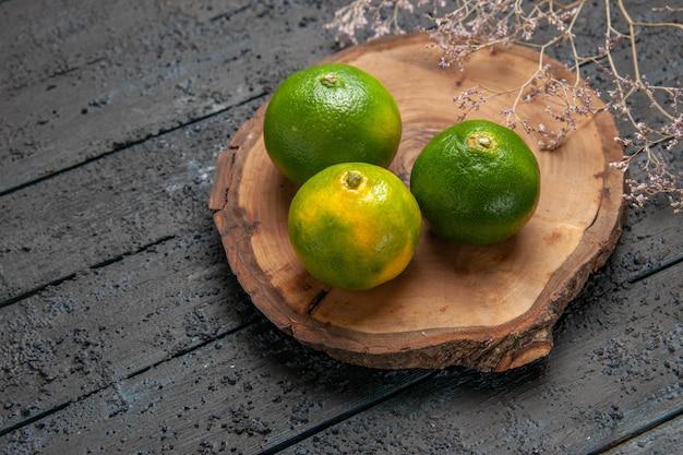 Vista laterale dall'alto lime a bordo lime su tavola di legno al centro del tavolo grigio accanto ai rami degli alberi