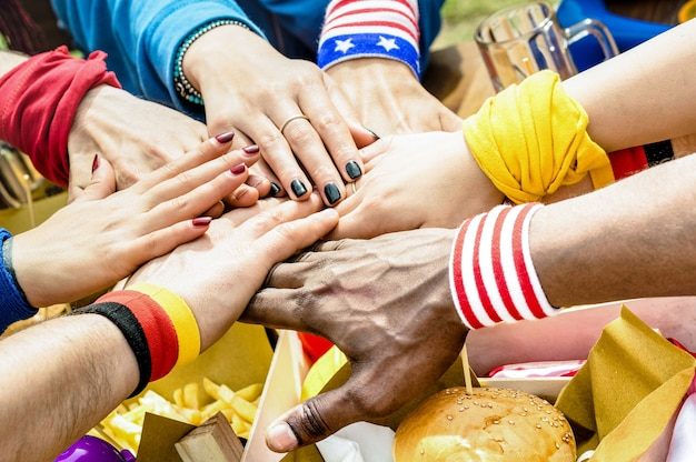길거리 음식을 공유하는 축구 후원자 친구의 다민족 손의 윗면보기