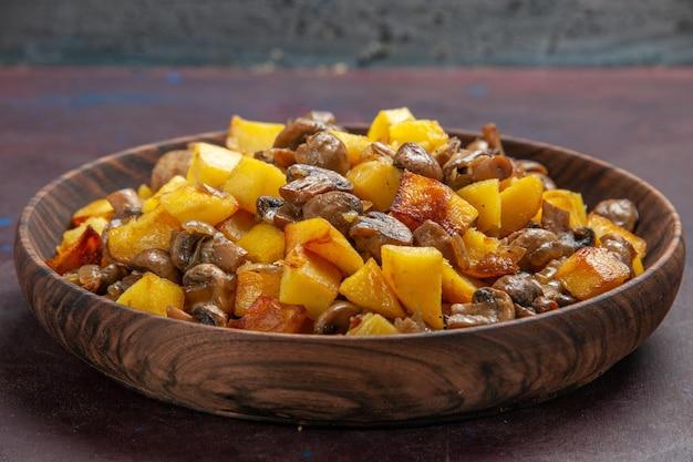 어두운 표면에 있는 그릇에 감자와 함께 버섯 버섯이 있는 위쪽 측면 보기 감자