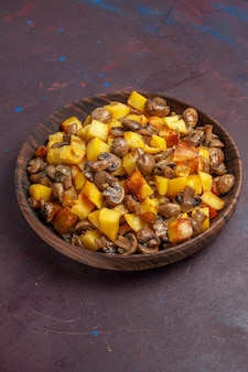 Top side view potatoes with mushrooms on the dark surface there is a brown bowl wih potatoes and mushrooms