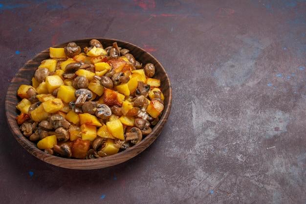Картофель с грибами, вид сверху, сбоку, на темной поверхности стоит миска с картофелем и грибами.
