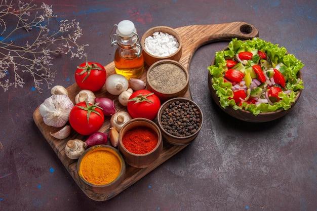 Vista laterale dall'alto insalata e spezie spezie diverse pomodori cipolle funghi e olio sul tagliere e insalata con verdure