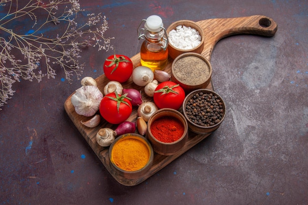 Vista laterale dall'alto spezie sul tagliere spezie diverse pomodori funghi cipolla e olio sul tagliere