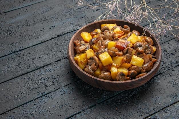 Vista laterale dall'alto ciotola di legno con cibo ciotola di legno con patate e funghi accanto ai rami al centro del tavolo
