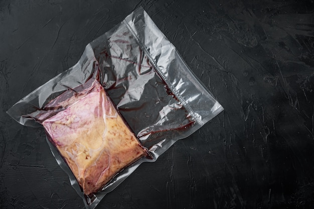 Top sirloin beef big cut in plastic pack, on black table, top view,