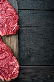 Top sirloin beef steaks cut, on black wooden table, top view,