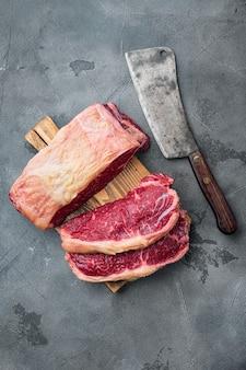 Нарезанные стейки из говяжьей вырезки на сером столе, вид сверху