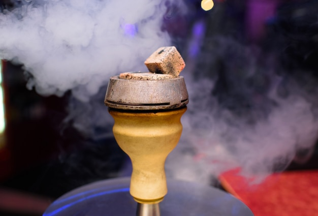 The top of a smoky and delicious hookah. a hookahman is preparing a hookah for restaurant guests.