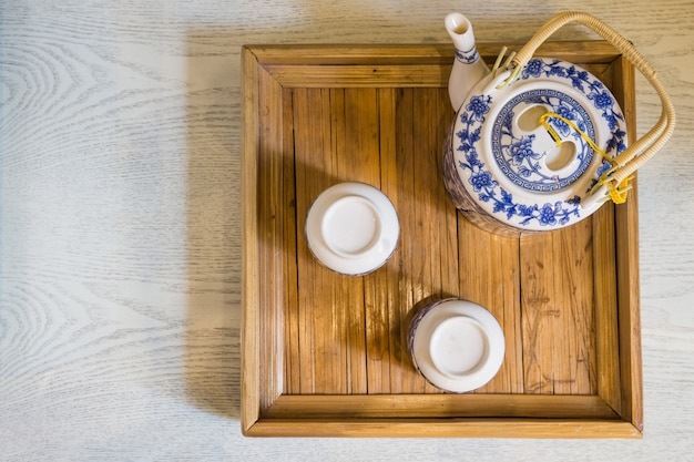 Top of traditional white cup of tea and teapot in wooden tray closeup on table