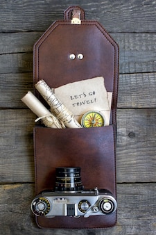 Top travel wooden background, bag, camera, map
