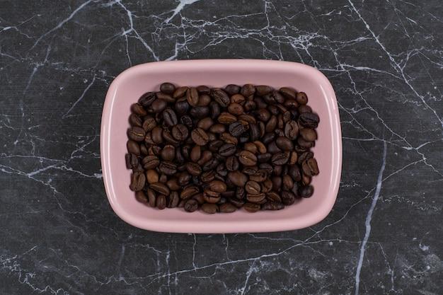 ピンクのボウルに茶色のコーヒーの種の写真を追加します。