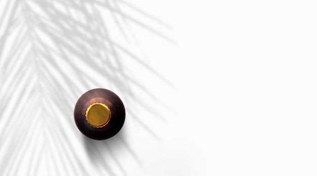 흰색으로 격리된 야자수 아래 짙은 갈색 맥주병을 위로 올려보세요.