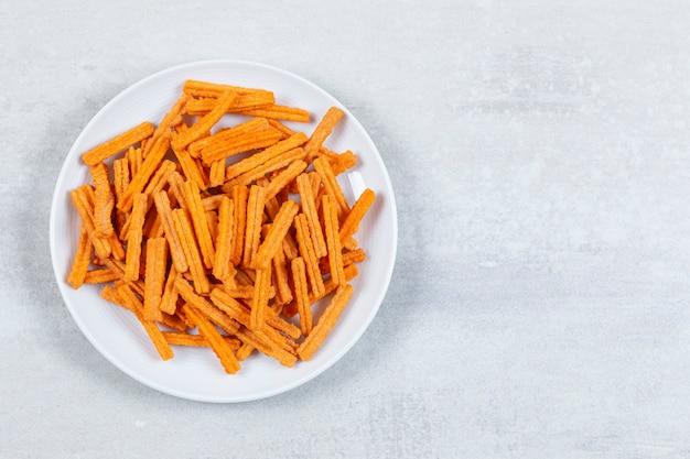 Vista superiore di patatine fritte fresche sul piatto bianco.