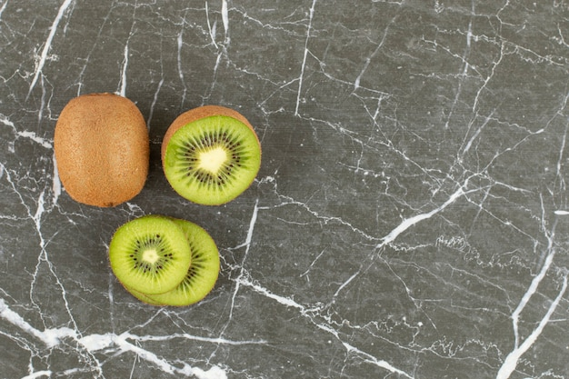 Top up view of fresh organic kiwis. whole, half cut and sliced.