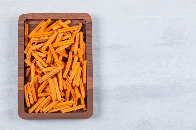 Vista dall'alto di patatine fritte sul piatto di legno.