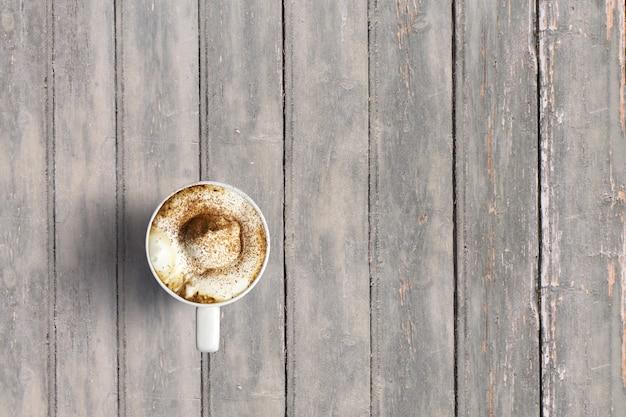 어두운 나무 빈티지 테이블에보기 이탈리아 카푸치노를 위로 가기. 음식이나 음료 개념 배경에 적합한 텍스트 복사 공간을 추가했습니다.