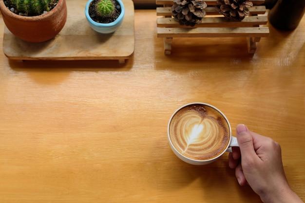 Вид сверху руки, держащей кофейную чашку латте-арт на коричневом деревянном столе с горшком кактуса, место для текста