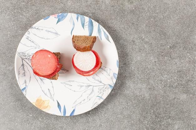 白いプレート上の手作りの新鮮なサンドイッチの上面図。