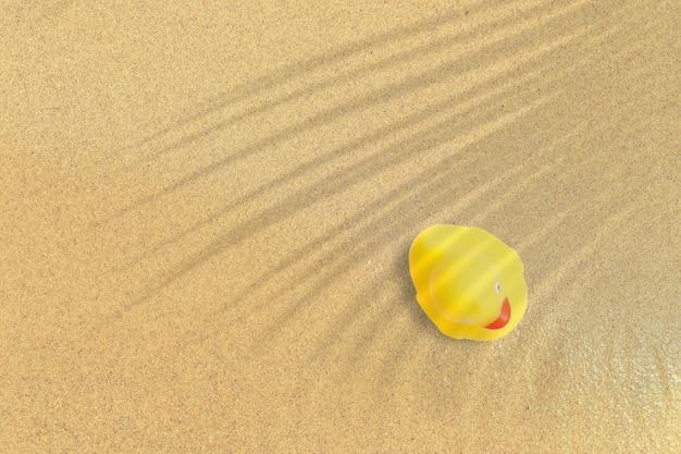 Вид сверху желтой резиновой утки на песчаном пляже. отпуск концепции фон.
