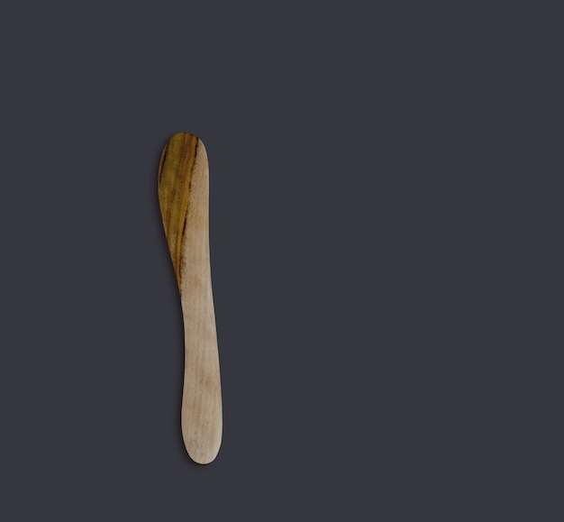 Top up view olive wooden butter knife isolated on black