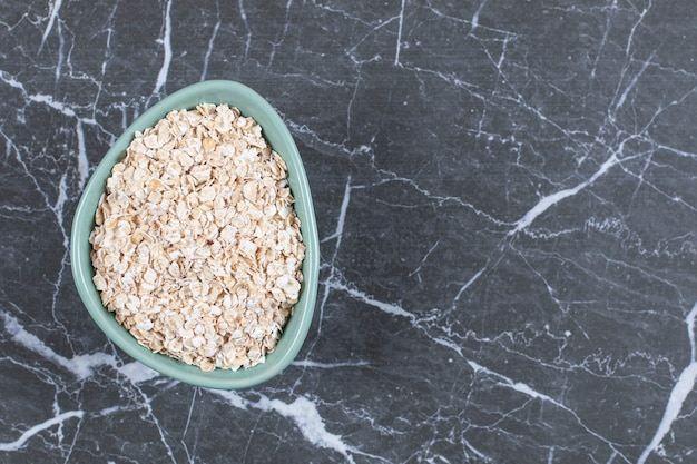 Top up view. rolled oats or oat flakes in wooden bowl on stone.