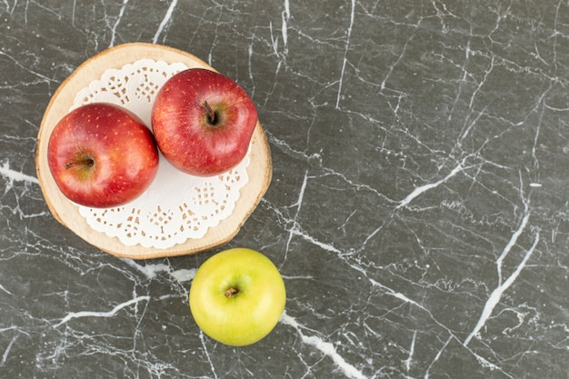 Top up view of two red and one green apple on wooden board.