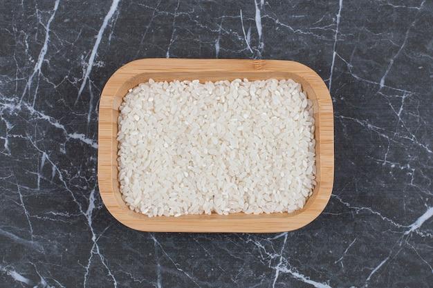 Vista superiore della ciotola di legno piena di riso crudo su pietra nera grigia.