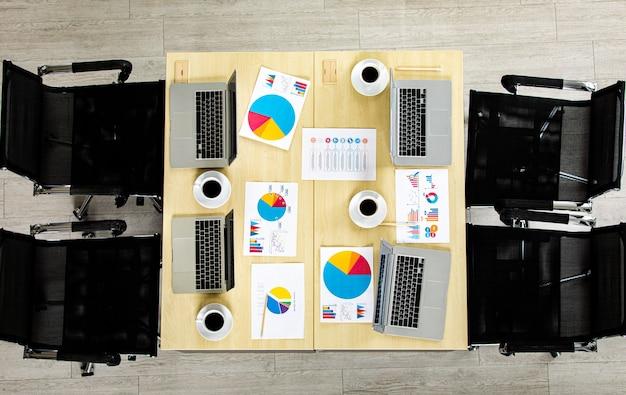상단 뷰 각도, 노트북 컴퓨터, 커피 컵, 그래프 및 차트 용지가 있는 나무 색상 작업 책상과 아무도 없습니다.