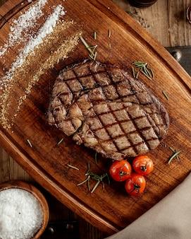 Сверху вид на стейк из говядины на деревянной доске