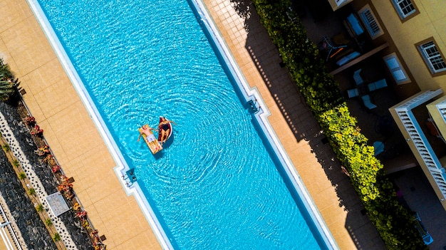 Top vertical view of swimming pool in hotel residence vacation with people adult senior lay down and enjoy with inflatables lilos mattress on blue water