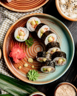 Top vie of sushi rolls with tempura shrimps avocado and cream cheese on a plate with ginger and wasabi