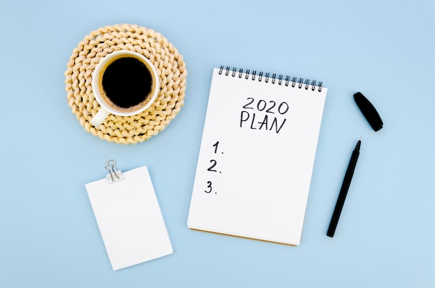 Top view 2020 resolutions plan with cup of coffee