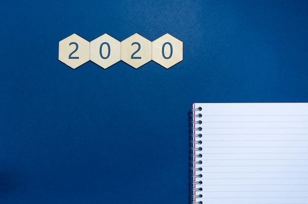 Top view of 2020 written on four wooden hexagons  with notepad and pen in a conceptual image for new years resolution. over blue background with copy space.