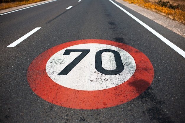 Top view of 70 km per hour, speed limit sign painted on dark asphalting road. perspective concept.