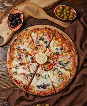 Top view of 8 pieces mixed pizza with olive, tomato, bell peppers
